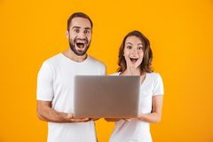 Portrait of lovely man and woman holding silver laptop, while standing isolated over yellow background royalty free stock images