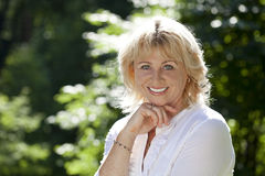 Portrait of lovely middle aged woman in the summer park Royalty Free Stock Photo