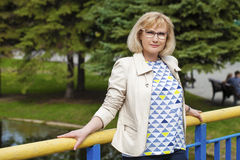 portrait of lovely middle aged woman in the summer park royalty free stock photos