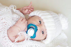 Portrait of lovely newborn with dummy in white knitted hat Stock Image