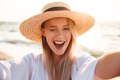 Portrait of lovely pleased blonde woman 20s in summer straw hat. Smiling and taking selfie while walking at sea coast Stock Image