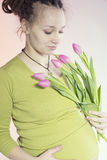 Portrait of lovely pregnant woman with tulips Stock Photos
