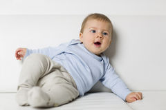 Portrait of lovely smiling baby boy lying on couch. Royalty Free Stock Photo