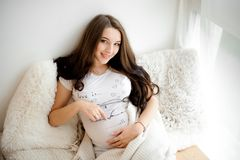 Portrait of a lovely smiling long-haired pregnant woman Stock Photos