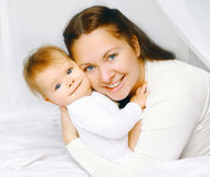 Portrait lovely smiling mother and baby in bed Royalty Free Stock Image