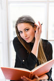 Portrait of lovely studying girl correcting hairstyle. Books and pens Stock Photography