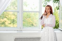Portrait of lovely woman posing in studio. Against the window dressed in wedding dress royalty free stock images