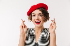 Portrait of a lovely woman wearing beret. Holding fingers crossed for good luck isolated over white background Stock Photo