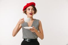Portrait of a lovely woman wearing red beret. Drinking tea from cup on a plate isolated over white background Stock Photography