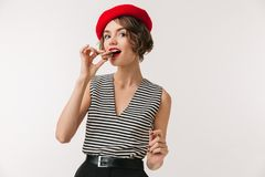 Portrait of a lovely woman wearing red beret. Eating cookies isolated over white background Royalty Free Stock Photos
