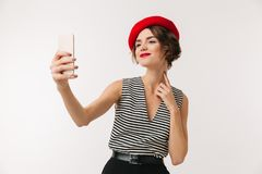 Portrait of a lovely woman wearing red beret. Taking a selfie isolated over white background Stock Photography