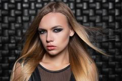 Portrait of a lovely young blonde woman. Posing in a studio dressed in a black leather suit royalty free stock photos