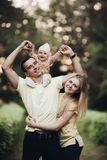 Portrait of lovely young family sitting together outside. stock photography