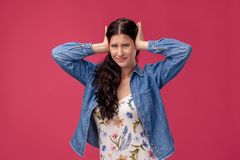 Portrait of a pretty young woman in a light dress and blue shirt standing on pink background in studio. People sincere. Portrait of a lovely young female in a stock images