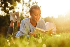 Portrait of a lovely young girl. With backpack laying on a grass at the park, reading a book Stock Photography