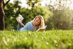 Portrait of a lovely young girl with backpack. Portrait of a lovely young girl laying on a grass at the park, reading a book, taking notes Royalty Free Stock Photo