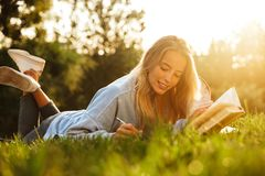 Portrait of a lovely young girl with backpack. Laying on a grass at the park, reading a book, taking notes Royalty Free Stock Photos