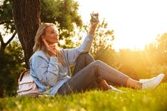 Portrait of a lovely young girl with backpack. Sitting on a grass at the park, taking selfie Stock Photography