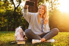 Portrait of a lovely young girl with backpack. Sitting on a grass at the park, taking selfie, showing peace Stock Photography