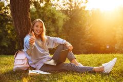 Portrait of a lovely young girl with backpack. Sitting on a grass at the park, using laptop computer, showing thumbs up Stock Photo