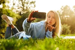 Portrait of a lovely young girl with book laying on a grass. At the park, taking selfie, sending kiss Stock Photos