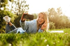 Portrait of a lovely young girl with book. Laying on a grass at the park, taking selfie, showing peace Royalty Free Stock Photography