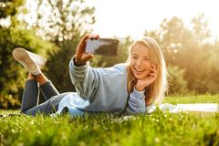 Portrait of a lovely young girl with book laying on a grass. At the park, taking selfie Stock Photo
