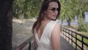 Portrait lovely young girl with brunette hair wearing sunglasses and long white summer fashion dress walking along a stock footage