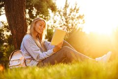 Portrait of a lovely young girl. Sitting on a grass at the park, reading a book Stock Photography