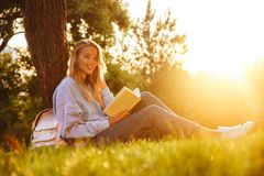 Portrait of a lovely young girl. Sitting on a grass at the park, reading a book, taking notes Stock Photo