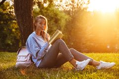 Portrait of a lovely young girl sitting on a grass. At the park, reading a book, taking notes Royalty Free Stock Photo