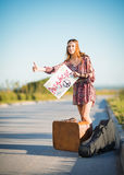 Portrait of lovely young hippie girl hitchhiking on a road Royalty Free Stock Photos