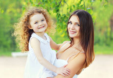 Portrait lovely young mother and cute daughter in sunny summer. Day Royalty Free Stock Photo