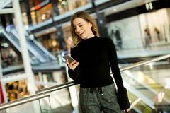 Lovely young woman looking on mobile phone in shopping center stock photography