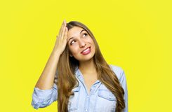 Portrait of lovely young woman looking up remembered something and holds head with hand over yellow background stock photo