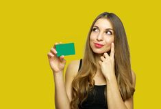Portrait of a lovely young woman showing credit card and looking away at copy space isolated over yellow background stock photo