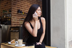 Portrait of a lovely young woman talking on cellphone while relaxing in coffee shop during breakfast Stock Images