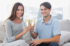 Portrait of lovers clinking their flutes of champagne Stock Photography