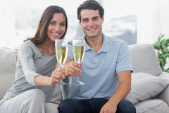 Portrait of lovers toasting their flutes of champagne. Sat on a couch Royalty Free Stock Photos