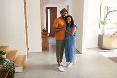 Portrait Of Loving African American Couple Hugging In Hall At Home
