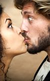 Portrait of a loving couple giving a kiss by surprise Royalty Free Stock Image