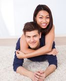 Portrait of loving couple lying on rug Royalty Free Stock Image