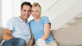 Portrait of a loving couple sitting on sofa in living room Stock Photos