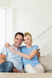 Portrait of a loving couple sitting on sofa in living room Stock Photography