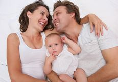 Portrait of a loving family holding cute baby in bed Stock Images