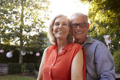 Portrait Of Loving Mature Couple In Back Yard Garden Stock Photo