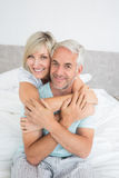 Portrait of a loving mature couple in bed Stock Photos
