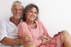 Portrait Of Loving Mature Couple Sitting Against Wall Royalty Free Stock Image