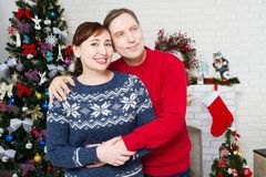 Portrait of loving middle aged couple in living room with christmas tree and decorated fireplace, loving family stock photography
