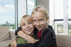 Portrait of loving siblings in dinosaur and vampire costumes at home Stock Photo